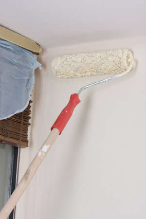 house painter using a paint roller, painting a wall in motion photo
