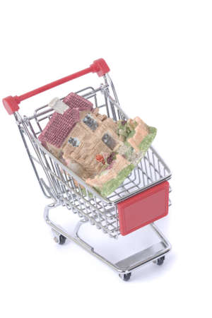 shopping cart trolley with house isolated on white photo
