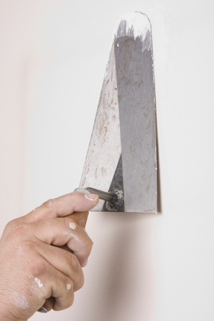putty: Putty Knife with Paste to Repair Wall Damage Stock Photo