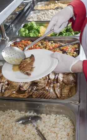 comedor escolar: Chef de pie detr�s de la estaci�n de servicio completo de comidas