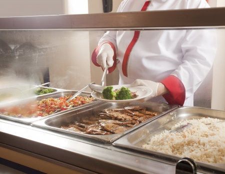 school lunch:  chef standing behind full lunch service station