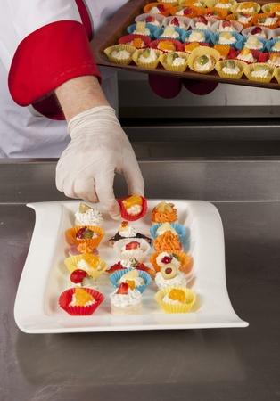 garnishing: chef garnishing canapes Stock Photo