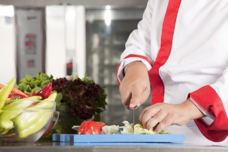 chef is preparing vegetable salad from a cabbage, tomato, cucumbers, carrot, parsley  photo