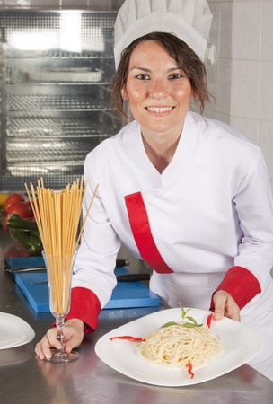 portrait of mid adult female chef in kitchen presenting dish  photo