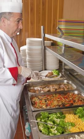 comedor escolar: Chef de pie detrás de la estación de servicio completo de comidas