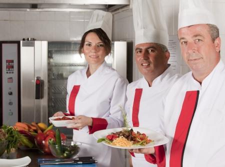 groep van jonge mooie professionele koks portret in industriële keuken