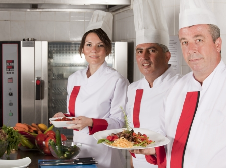 hotel service: group of young beautiful professional chefs portrait in industrial kitchen