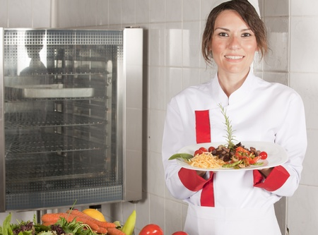 portrait of female chef in kitchen presenting dish  photo