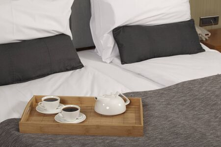Tray with coffee on a bed in a hotel room  photo