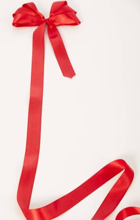 Shiny red satin ribbon on white background with copy space photo