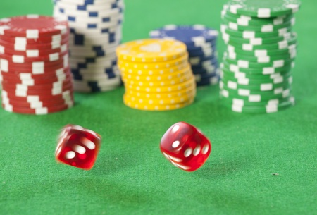 casino table: Rolling red dice on a casino table with chips Stock Photo