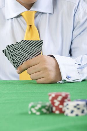 card player: card player with yellow tie  gambling casino chips on green felt background selective focus  Stock Photo