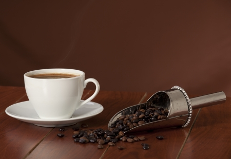 Coffee cup with coffee beans on the wooden table  photo