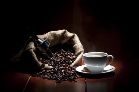 cafe colombiano: taza de café con granos en un fondo oscuro Foto de archivo