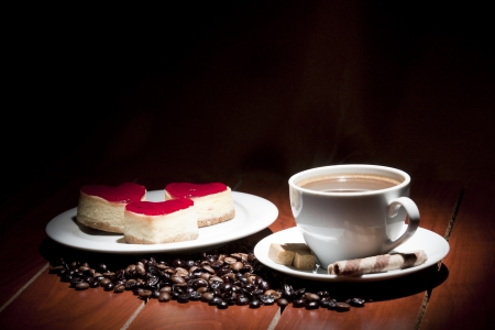 valentine day cup of coffee: cake  on plate and cup of coffee on wooden table