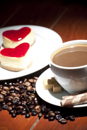 cake  on plate and cup of coffee on wooden table  photo