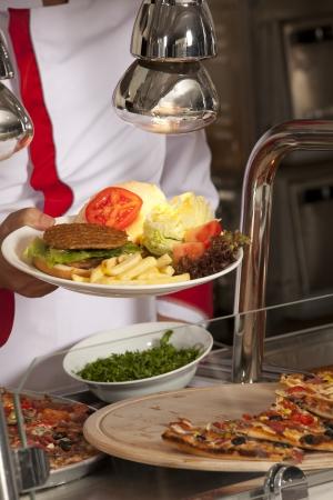 comedor escolar: chef de pie detrás de la hamburguesa y la pizza estación Foto de archivo