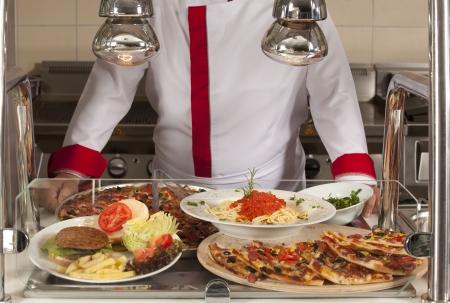 comedor escolar: chef de pie detrás de la hamburguesa y la pizza de estaciones de servicio Foto de archivo