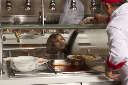 canteen: Students in cafeteria line trying to take her healthy meal  Stock Photo