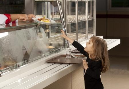 comedor escolar: Los estudiantes en línea de la cafetería tratando de tomar su comida saludable Foto de archivo
