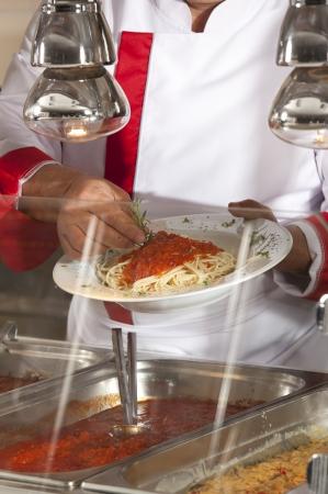 comedor escolar: chef de pie detrás de la estación de servicio completo de almuerzo