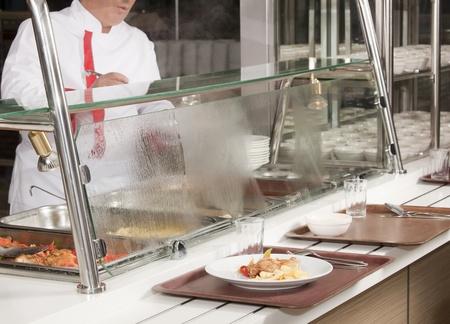 school canteen: chef de pie detrás de la estación de servicio completo de almuerzo