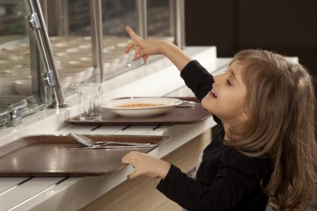 comedor escolar: niña en línea de la cafetería tratando de tomar su comida saludable Foto de archivo