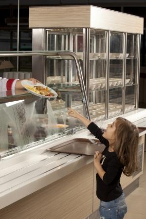 comedor escolar: ni�a en l�nea de la cafeter�a tratando de tomar su comida saludable Foto de archivo