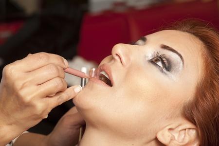 make up artist: Young beautiful bride applying wedding make-up by make-up artist