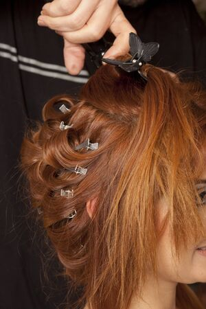 Close up of stylist s hand using curling iron for hair curls  photo