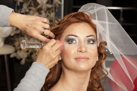 Young beautiful bride applying wedding make-up by make-up artist  photo