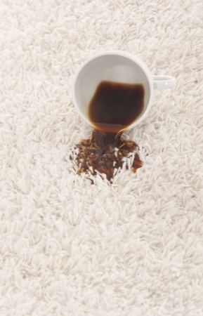 A glass of spilled coffee on brand new carpet is sure to leave a stain   photo
