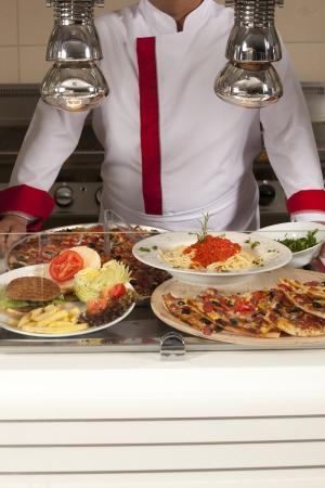 comedor escolar: chef de pie detrás de hamburguesa, pizza de espaguetis y la estación