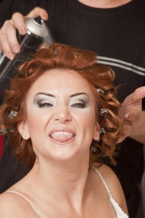 bride having hairdo on her wedding day photo