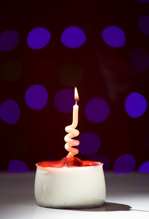 hundreds and thousands: happy birthday cake shot on a red blurred background with candles