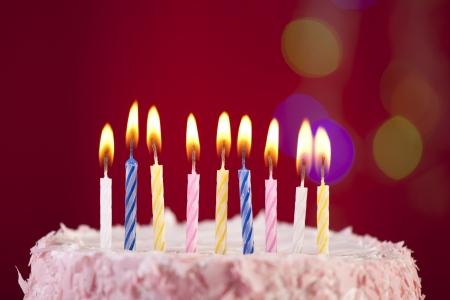 torta con candeline: torta di compleanno felice girato su uno sfondo rosso con le candele