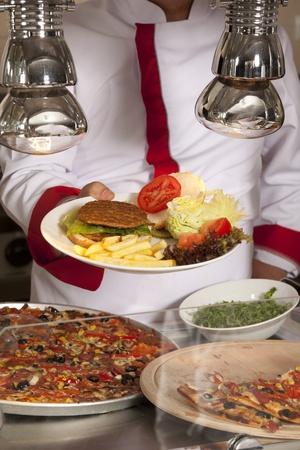 comedor escolar: chef de pie detrás de hamburguesas, espagueti y de la estación de pizza Foto de archivo
