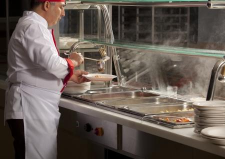 comedor escolar: chef de pie detr�s de la estaci�n de servicio de almuerzo completo
