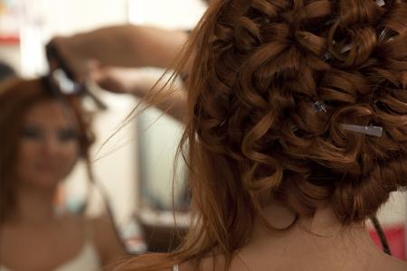 Stylist: Novia caucásica hermosa está preparando para la boda ceremony.beautiful novia joven morena prepararse para el evento