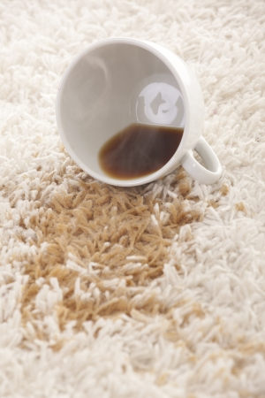A glass of spilled coffee  on brand new carpet is sure to leave a stain. Stock Photo