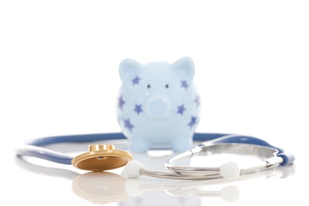 surgery expenses: Piggy bank and stethoscope isolated on white