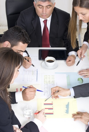 Businesspeople working together at meeting, discussing document Stock Photo - 19387237