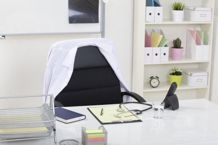 office equipment: Doctor office table desk and black chair with stethoscope  and white paper