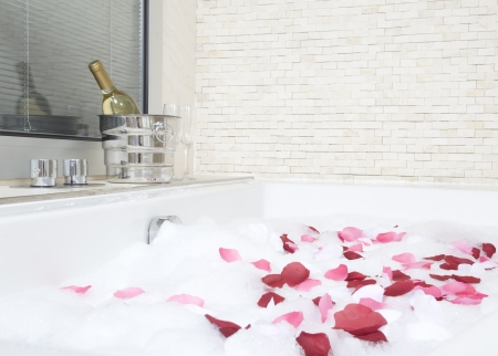 A relaxing bath with rose petals ,wine and glassess photo