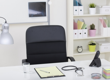 Doctor office table desk and black chair with stethoscope  and white paper photo