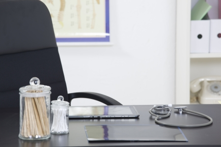 Doctors office desk with medical supplies documents stethoscope photo