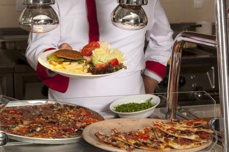 comedor escolar: chef de pie detr?s de hamburguesa, pizza de espaguetis y la estaci?n Foto de archivo
