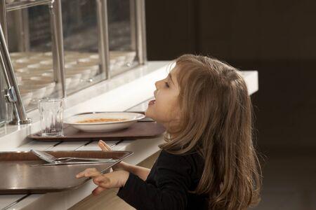 comedor escolar: ni?a en la cafeter?a de la escuela esperando el almuerzo Foto de archivo