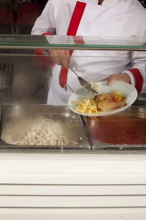 school cafeteria: chef standing behind full lunch service station