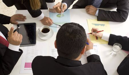 point of view: Businesspeople working together at meeting, discussing document Stock Photo